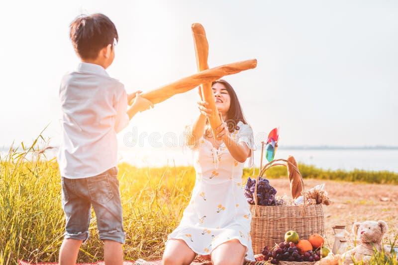 De moeder en de zoon spelen het schermen met brood samen wanneer picknick bij in openlucht dichtbij meer of rivier Mensenlevensst stock foto