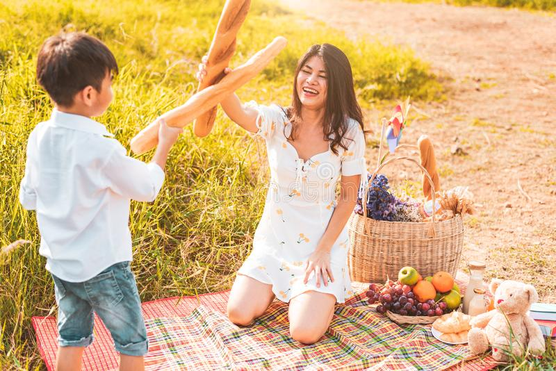 De moeder en de zoon spelen het schermen met brood samen wanneer picknick bij in openlucht dichtbij meer of rivier Mensenlevensst stock afbeelding