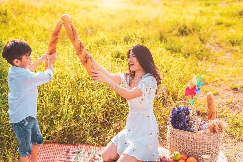 De moeder en de zoon spelen het schermen met brood samen wanneer picknick bij in openlucht dichtbij meer of rivier Mensenlevensst stock afbeeldingen