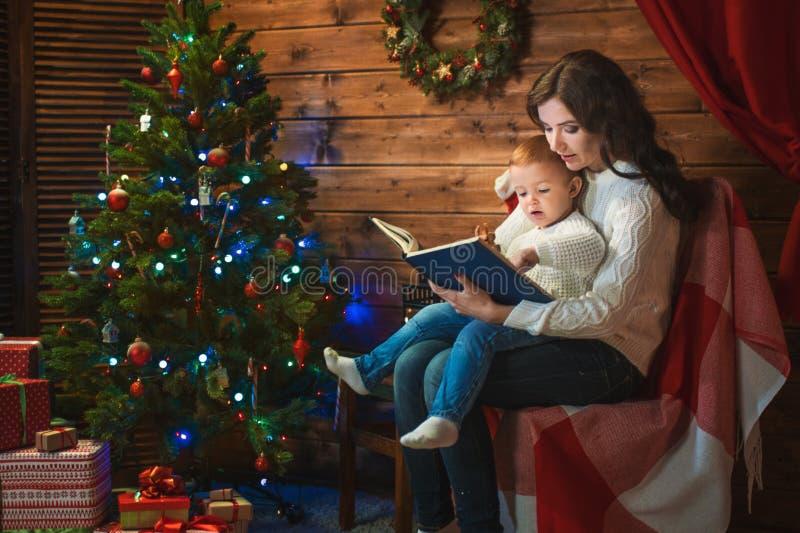 De moeder en de zoon vieren Kerstmis in een verfraaid huis met a.c. stock foto