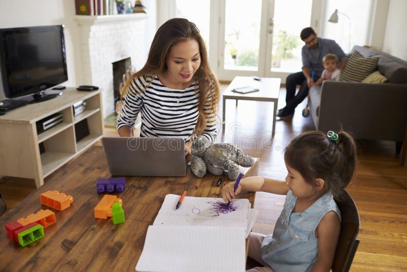 De moeder gebruikt thuis Laptop terwijl Vader Plays With Children stock afbeelding