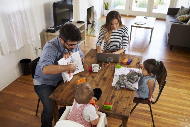 De moeder gebruikt thuis Laptop terwijl Vader Plays With Children stock fotografie