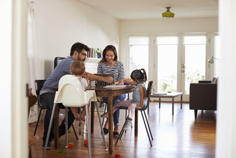 De moeder gebruikt thuis Laptop terwijl Vader Plays With Children royalty-vrije stock fotografie