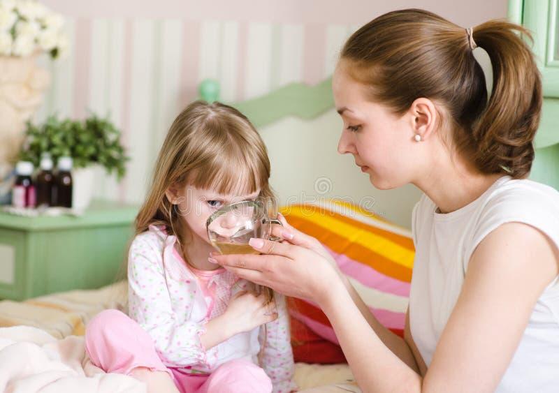 De moeder geeft aan drank aan het zieke kind royalty-vrije stock afbeeldingen