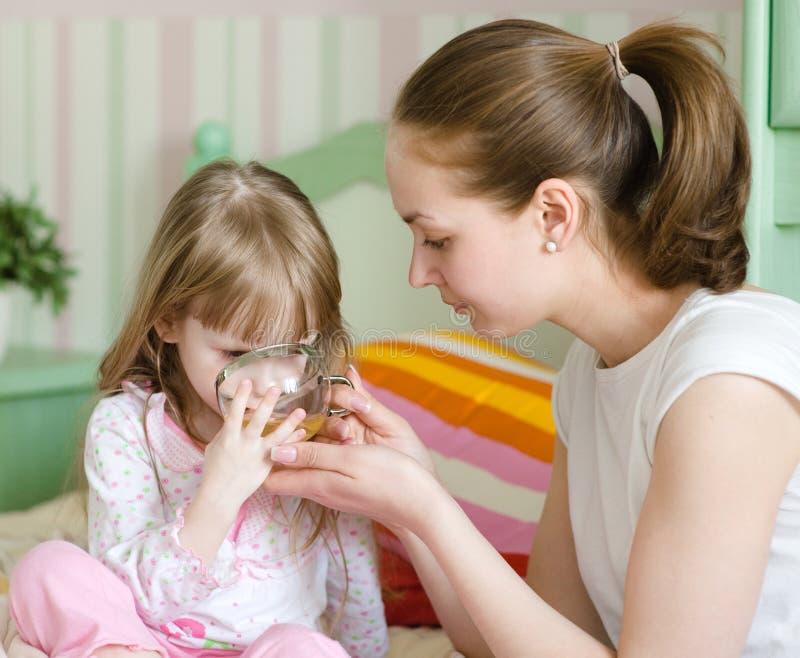 De moeder geeft aan drank aan het zieke kind royalty-vrije stock fotografie