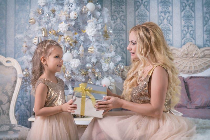 De moeder geeft een Kerstmisgift aan haar dochter stock foto's