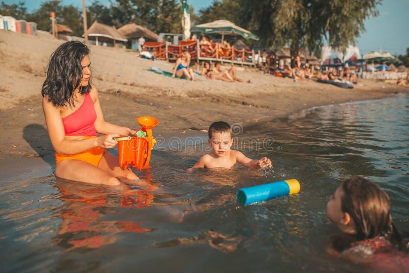 De moeder, haar zoon en dochter hebben pret in het water royalty-vrije stock foto