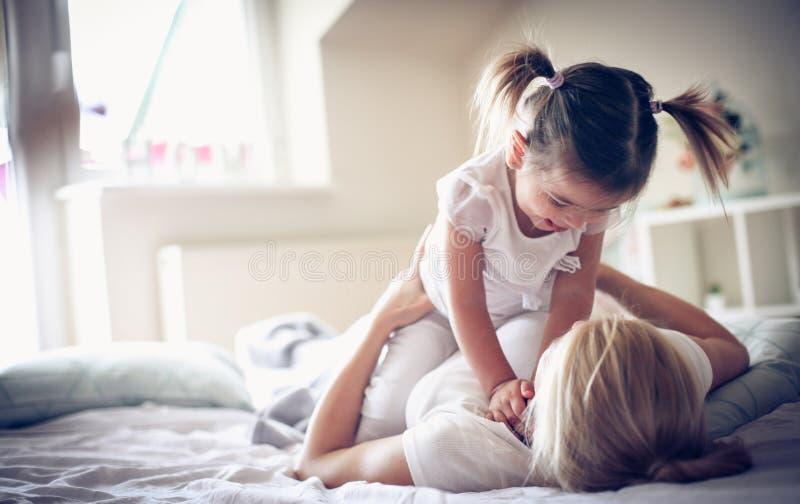 De moeder heeft het spelen bij ochtend met haar babymeisje stock foto