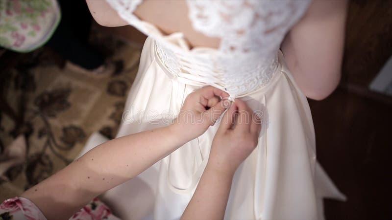 De moeder helpt de bruid om op een huwelijkskleding te zetten voorraad De handen binden een korset van een huwelijkskleding stock illustratie