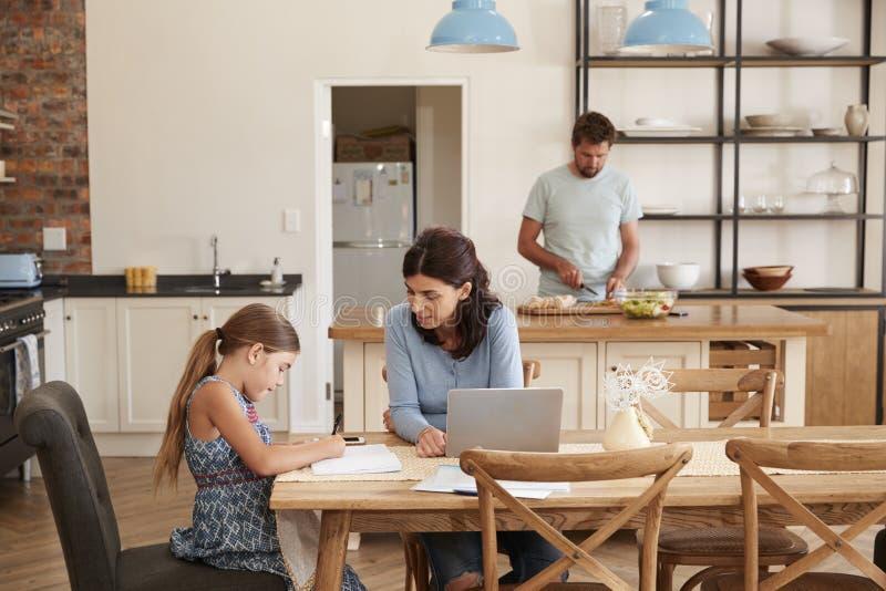 De moeder helpt Dochter met Thuiswerk als Vader Makes Meal royalty-vrije stock foto