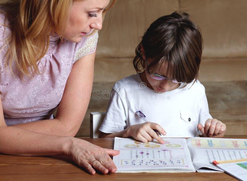 De moeder helpt haar zoon met thuiswerk stock fotografie
