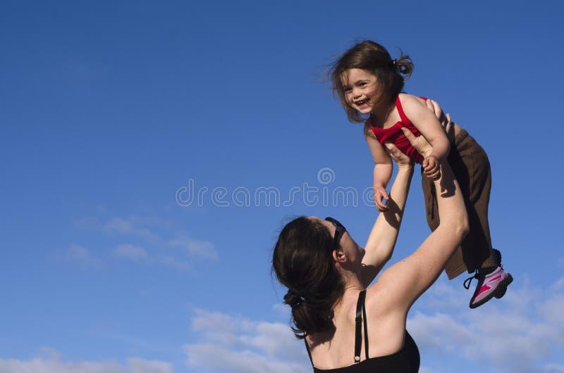 De moeder houdt haar dochter in de lucht tegen royalty-vrije stock foto