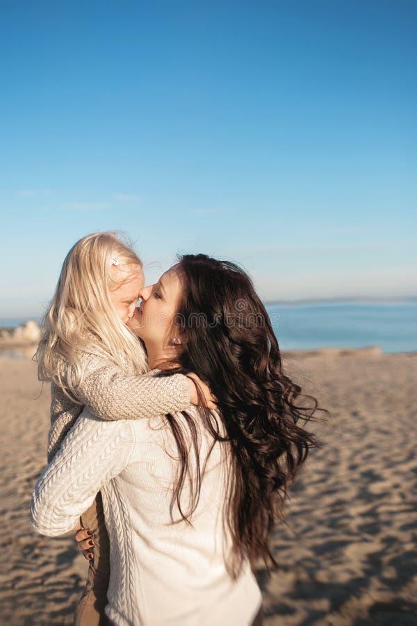 De moeder houdt op handen en kust haar weinig dochter royalty-vrije stock fotografie