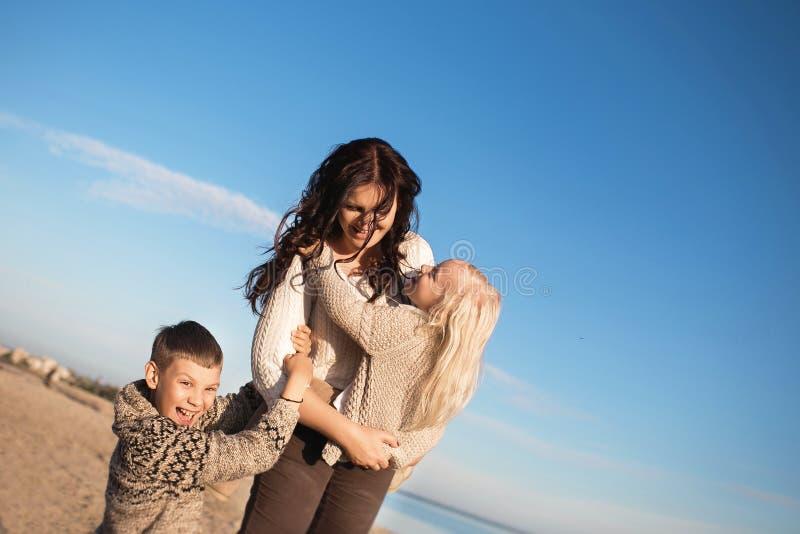 De moeder houdt op handen zijn kleine dochter en de zoon houdt aan hun stock foto