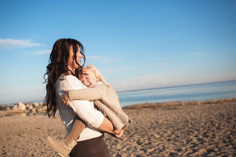 De moeder houdt op handen zijn kleine dochter en glimlacht op een strand stock afbeelding