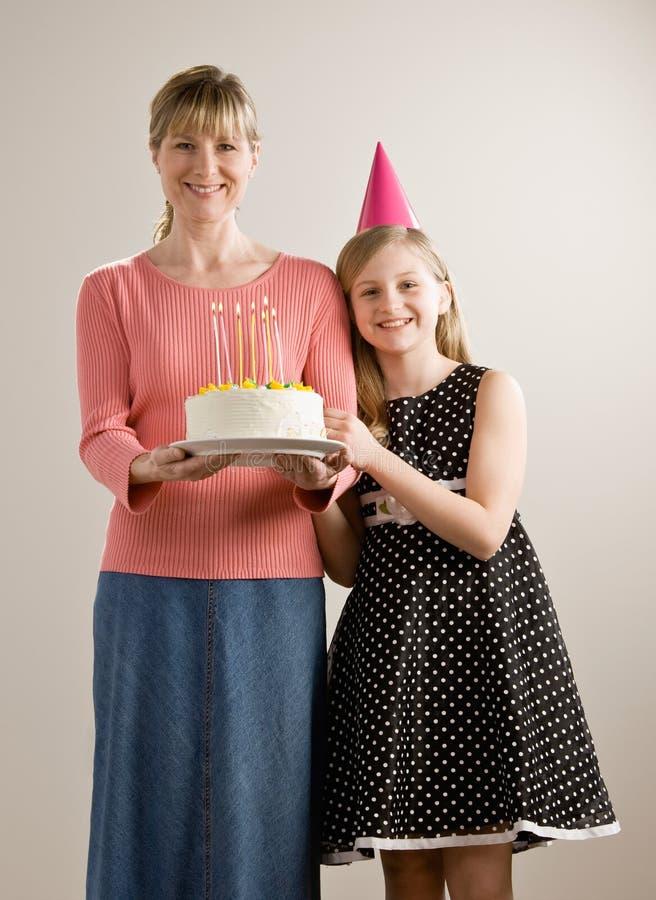 De moeder houdt verjaardagscake voor dochter stock afbeelding
