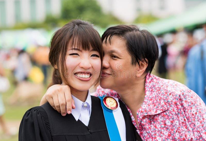 De moeder kust haar dochter met vreugde voor haar doctoraal examen stock afbeelding