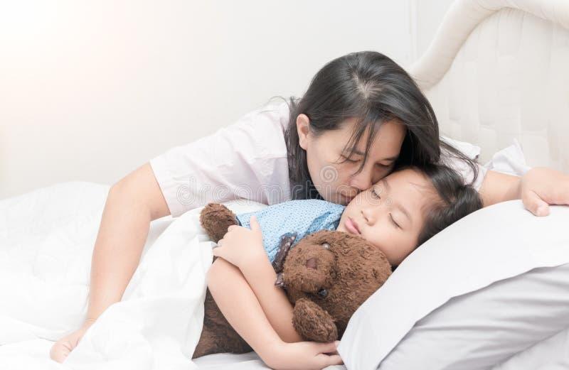De moeder kust haar dochter in wang terwijl het leggen op bed royalty-vrije stock fotografie