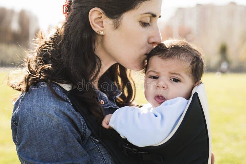 De moeder kust haar weinig baby royalty-vrije stock fotografie