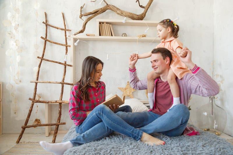 De moeder leest een boek en glimlacht terwijl samen thuis het doorbrengen van tijd stock foto