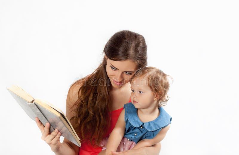 De moeder leest een boek met haar dochter stock foto's