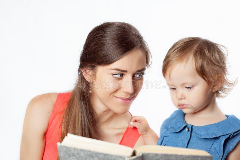De moeder leest een boek met haar dochter royalty-vrije stock afbeelding