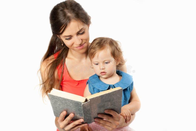 De moeder leest een boek met haar dochter stock afbeelding