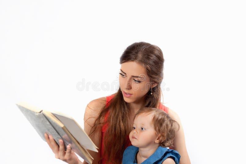 De moeder leest een boek met haar dochter stock foto