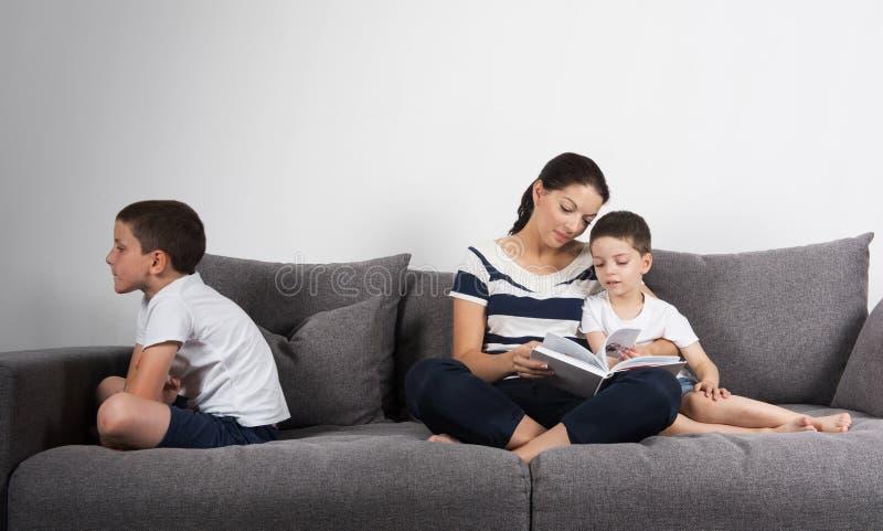 De moeder leest een interessant boek met haar zonen Jaloersheidsconcept royalty-vrije stock fotografie