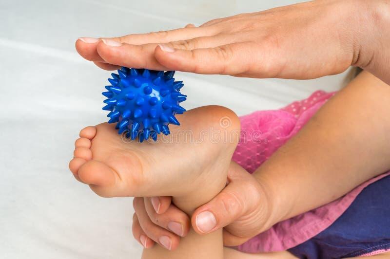 De moeder maakt voetmassage met blauwe massagebal royalty-vrije stock fotografie