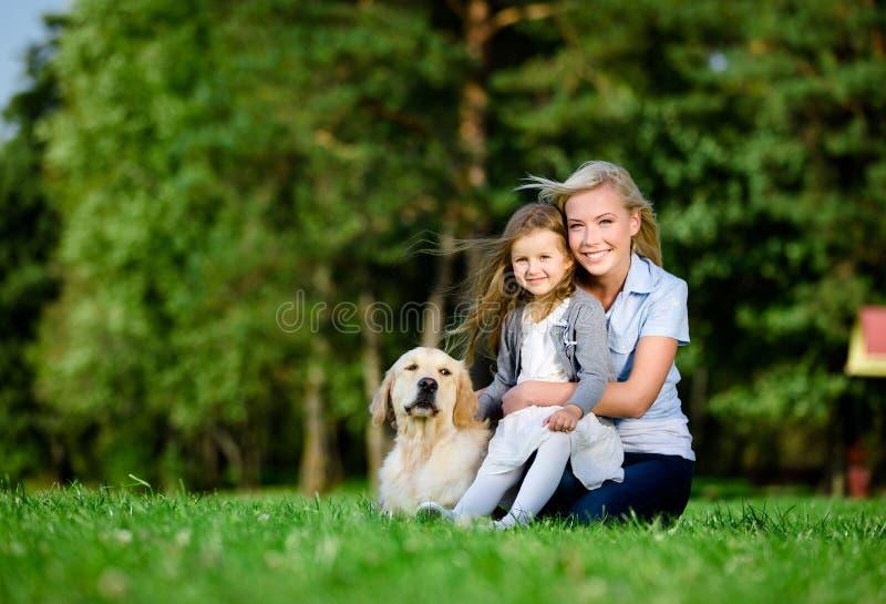 De moeder met dochter en Labrador zijn op het gras royalty-vrije stock afbeeldingen