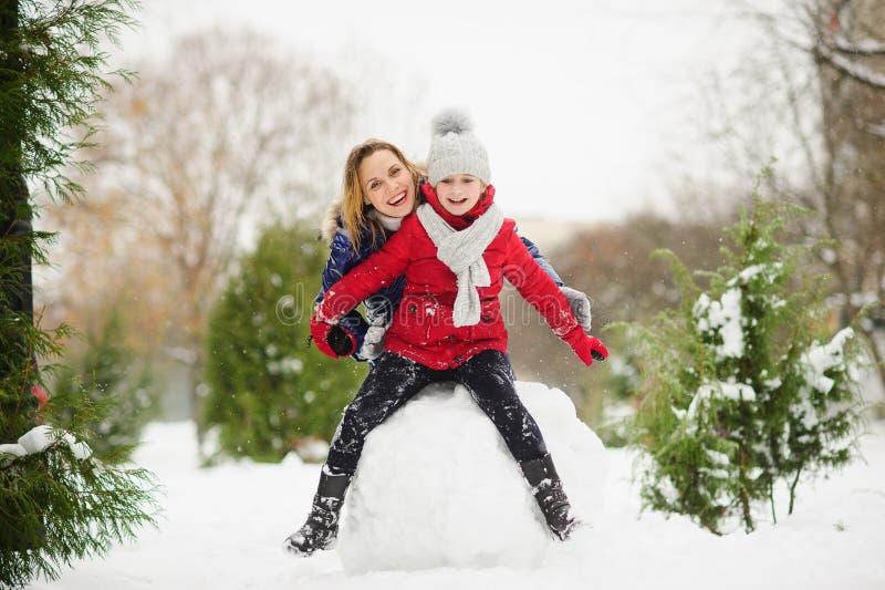 De moeder met dochter van jongere schoolleeftijd bouwt een sneeuwman in het park stock afbeelding