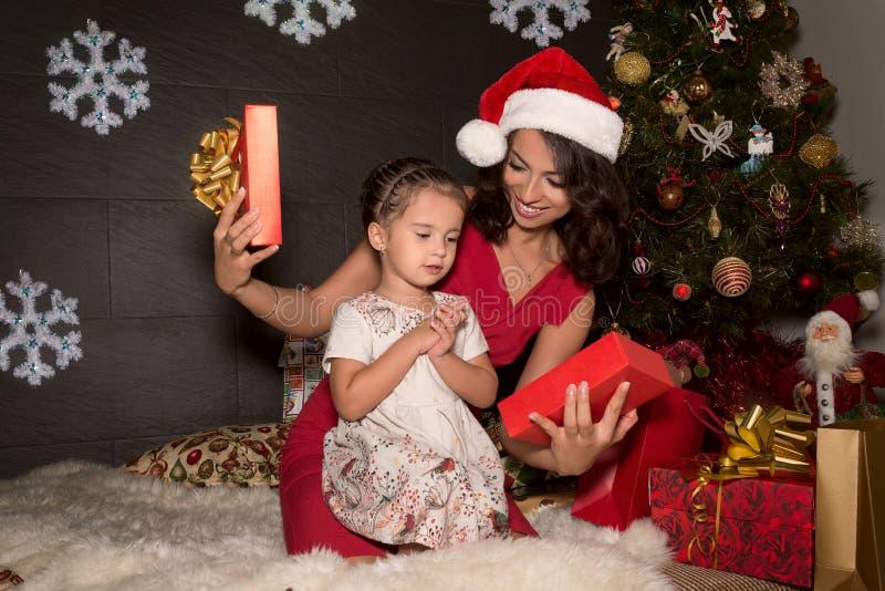 De moeder met dochters opent een Kerstmisgift stock foto's