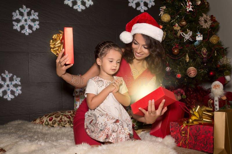 De moeder met dochters opent een Kerstmisgift royalty-vrije stock fotografie