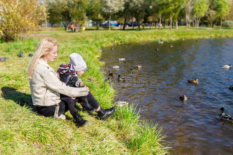 De moeder met dochterzitting op gras en het bekijken meer met eenden royalty-vrije stock fotografie