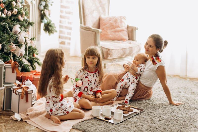 De moeder met een baby op haar handen zit o het tapijt met haar twee dochters zich in pyjama's etend koekjes met cacao kleedde stock fotografie