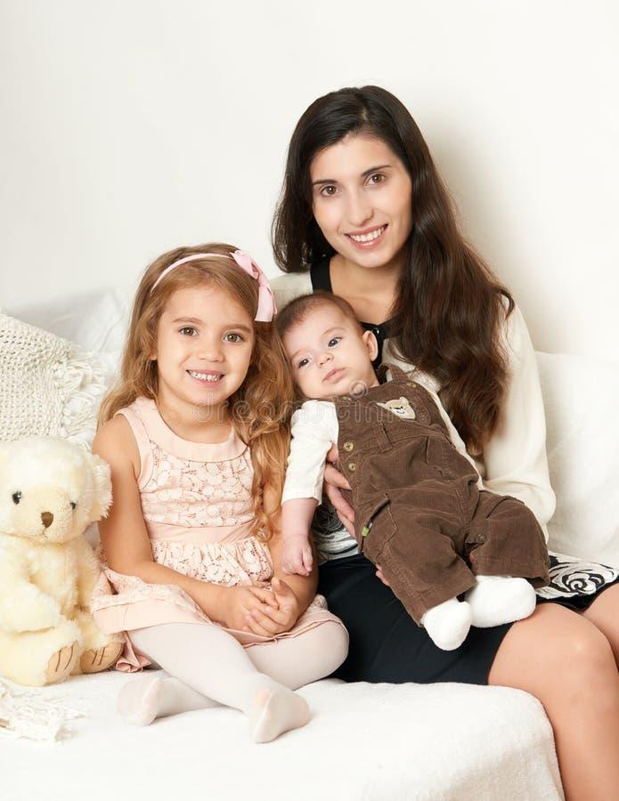 De moeder met haar kinderen zit in het bed met teddybeer, gelukkig familieportret royalty-vrije stock afbeeldingen