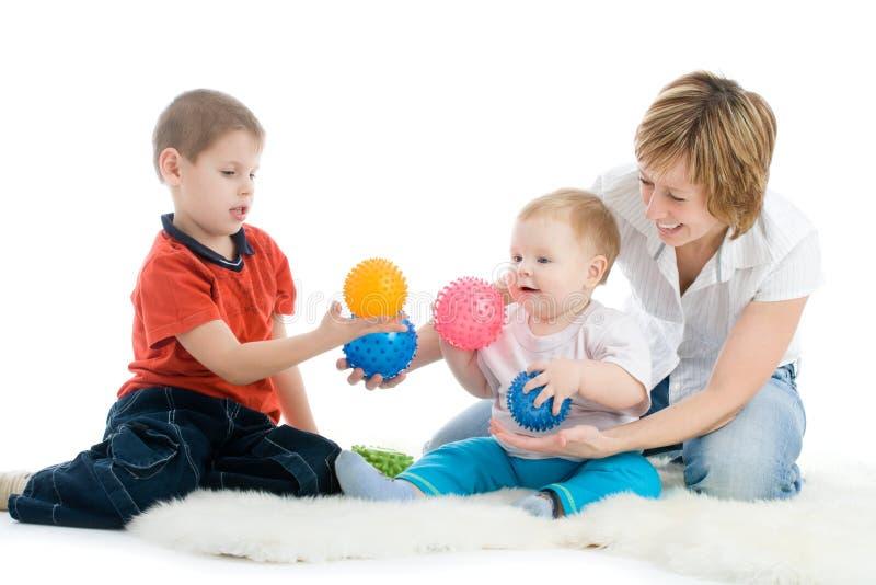 De moeder met haar zonen geniet van met kleurrijke ballen stock foto's