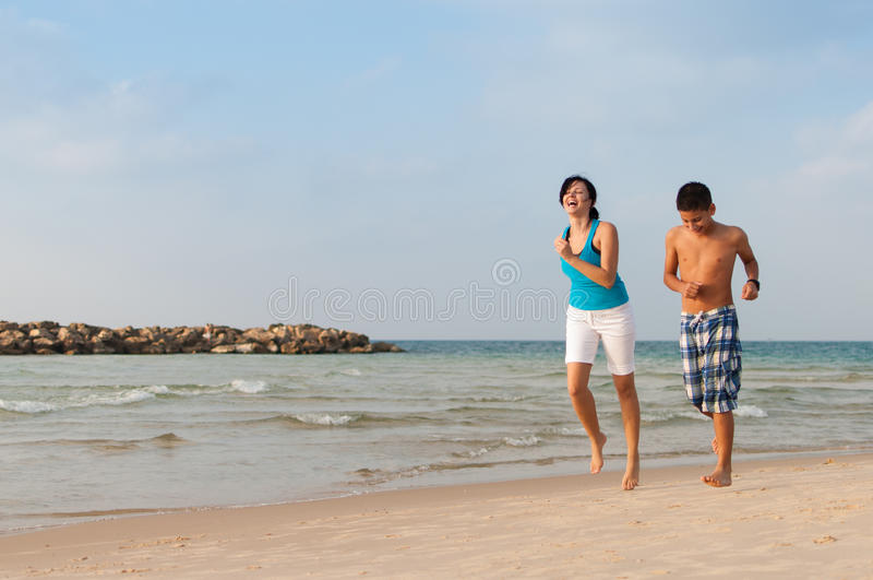 De moeder met haar zoon loopt op het strand stock afbeeldingen