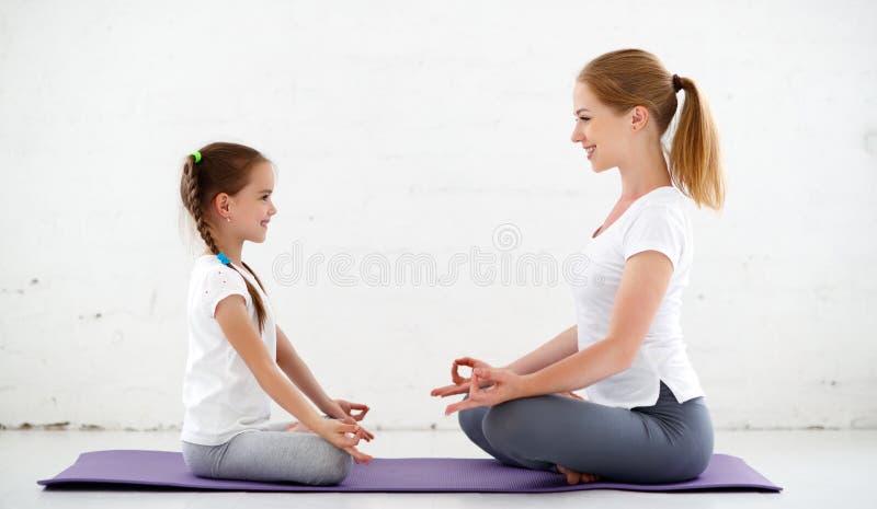 De moeder met kind het praktizeren yoga in lotusbloem stelt royalty-vrije stock afbeelding