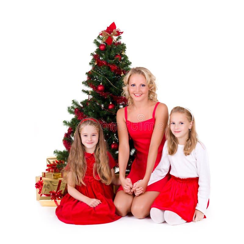 De moeder met kinderen zit dichtbij Kerstboom. royalty-vrije stock afbeeldingen