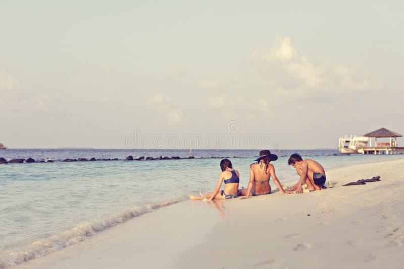 De moeder met twee kinderen ontspant op een strand stock foto's