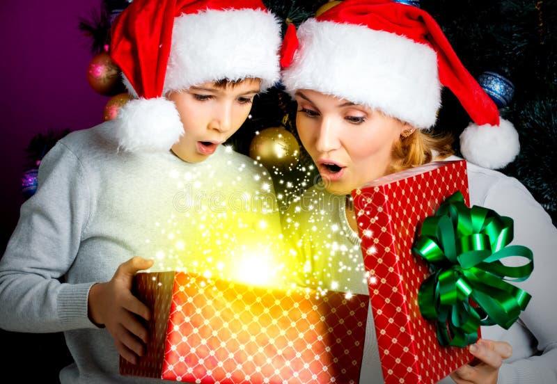 De moeder met weinig kind opent de doos met giften op Kerstmis stock afbeeldingen