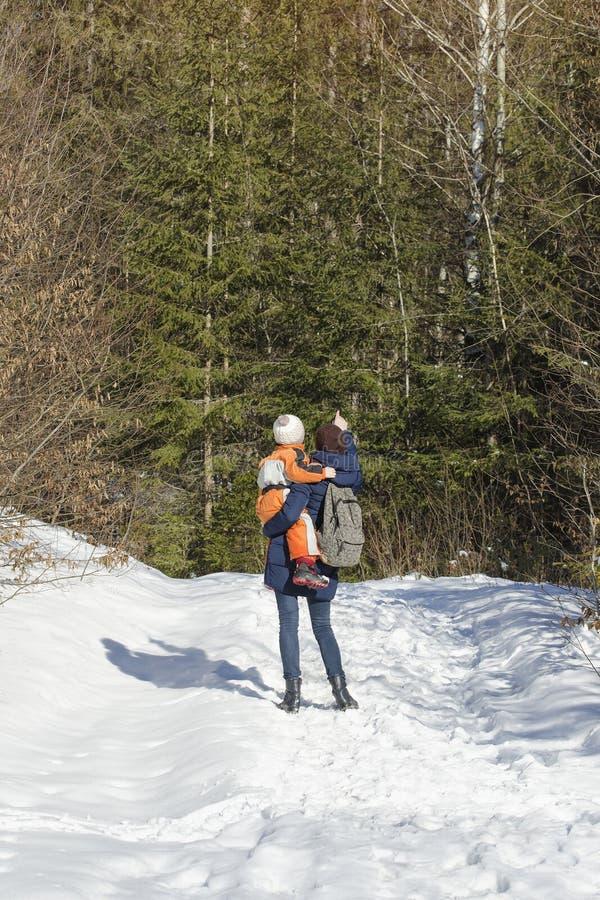 De moeder met zoon in wapens en rugzak bevindt zich tegen de achtergrond van naald bos en snow-covered weg De dag van de winter royalty-vrije stock afbeelding
