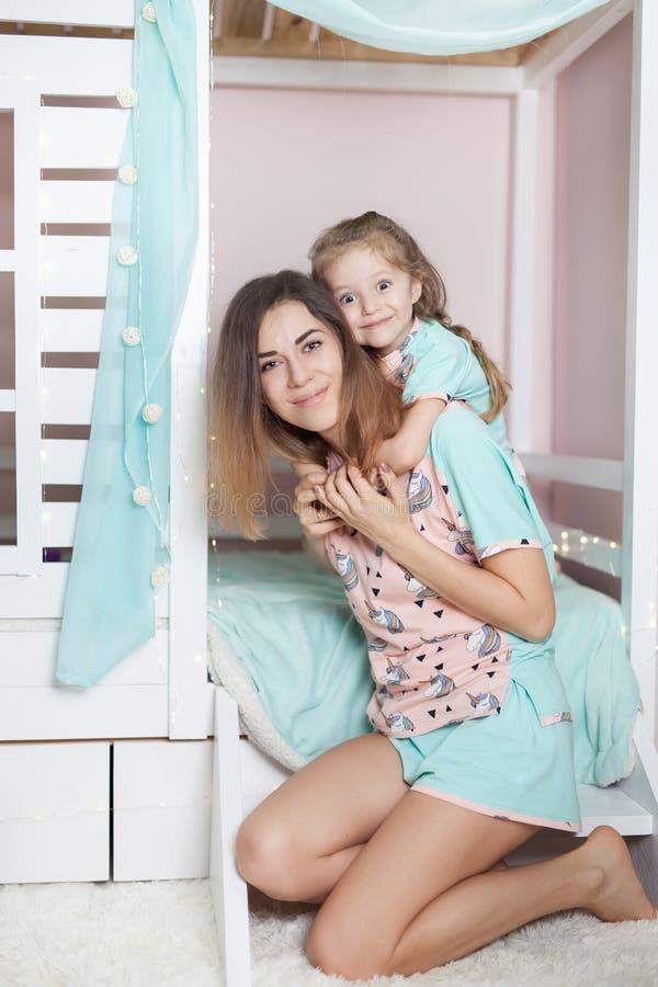 De moeder omhelst haar jong geitje gekleed in pyjama's klaar voor slaap royalty-vrije stock afbeeldingen