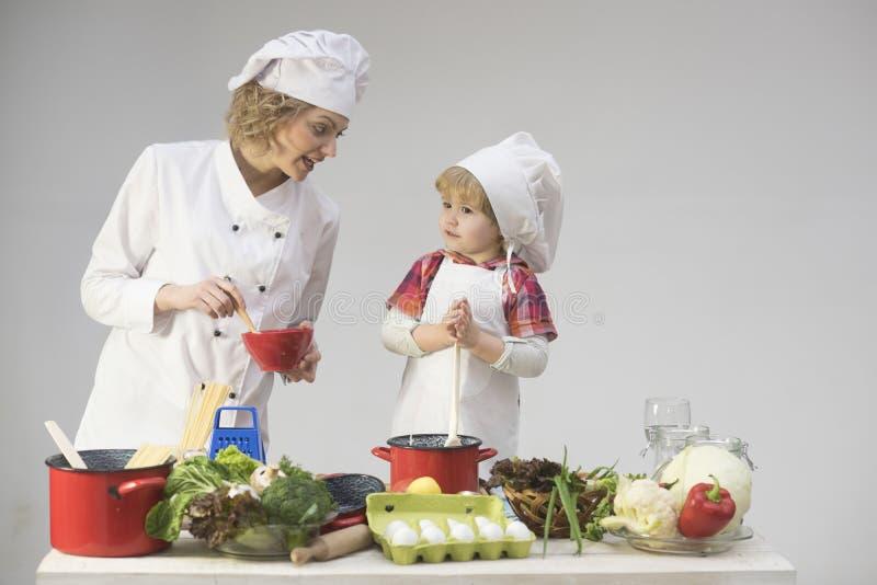 De moeder onderwijst zoon om op lichte achtergrond te koken stock foto's