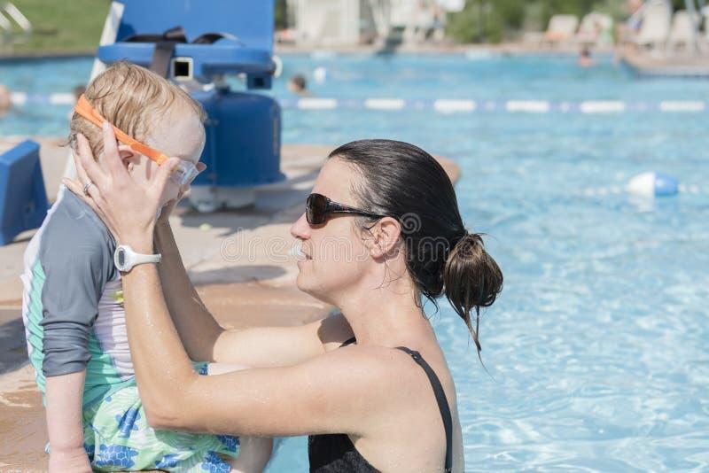 De moeder past haar Peuter Son& x27 aan; s Beschermende brillen aangezien hij Bereid wordt te spelen royalty-vrije stock fotografie