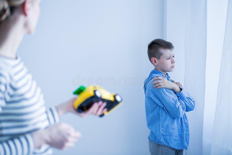De moeder probeert om zoon aan te moedigen om te spelen stock afbeelding