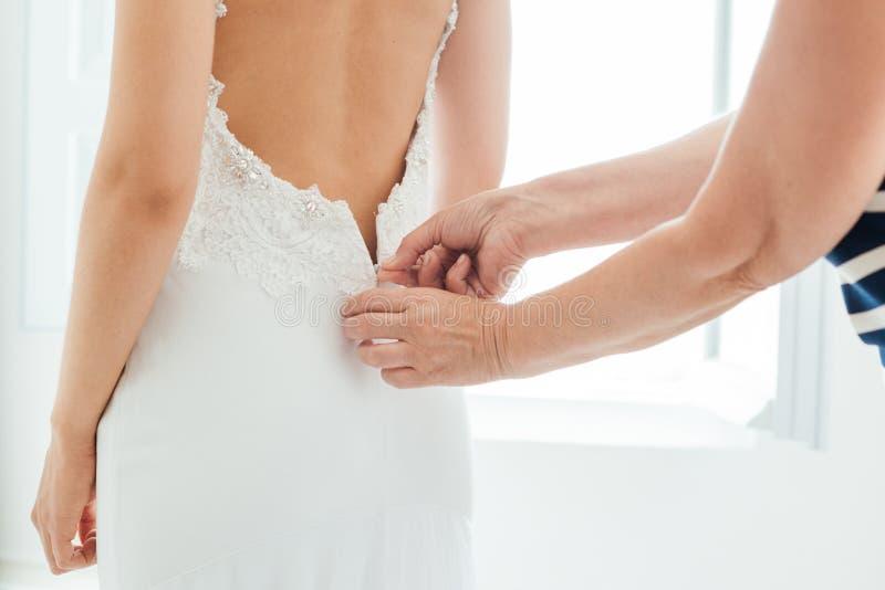 De moeder` s hand kleedt de bruid royalty-vrije stock foto
