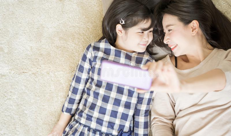 De moeder is selfie met haar weinig dochter die een smartphonecamera met behulp van terwijl oogcontact met dochter Aziatisch fami royalty-vrije stock foto